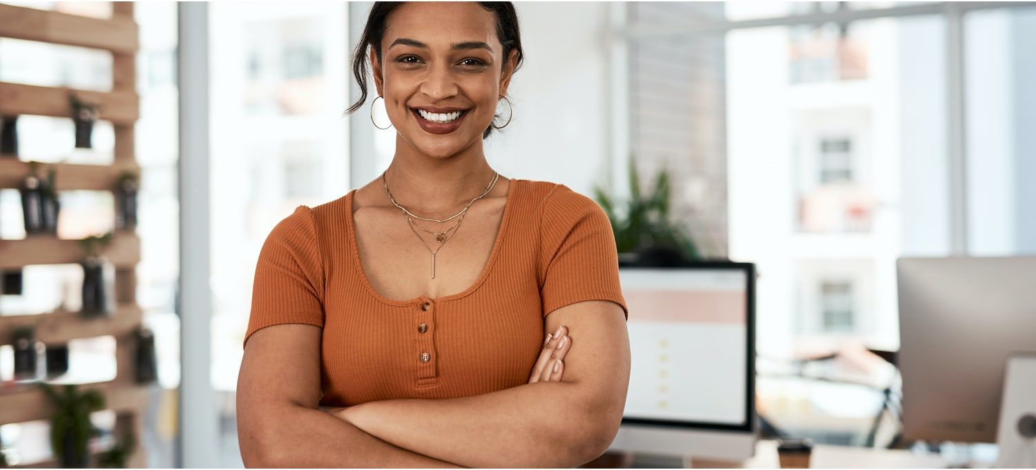 A smiling UX strategist in an orange shirt stands with their arms crossed next to their desk in a design office
