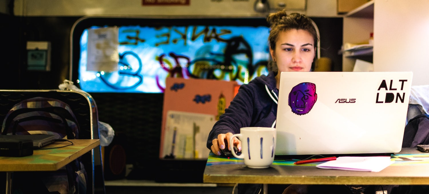 A young woman sits at a table in a cafe writing her resume on a laptop computer with stickers on it. She has a cup of coffee in front of her on the table.