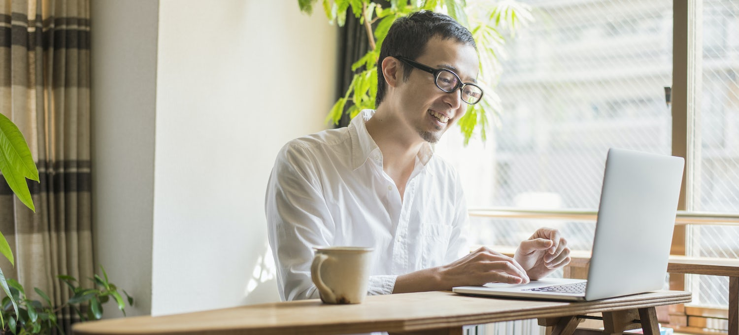 A man in glasses and a white shirt sits at his laptop in a sunny office working a cybersecurity job