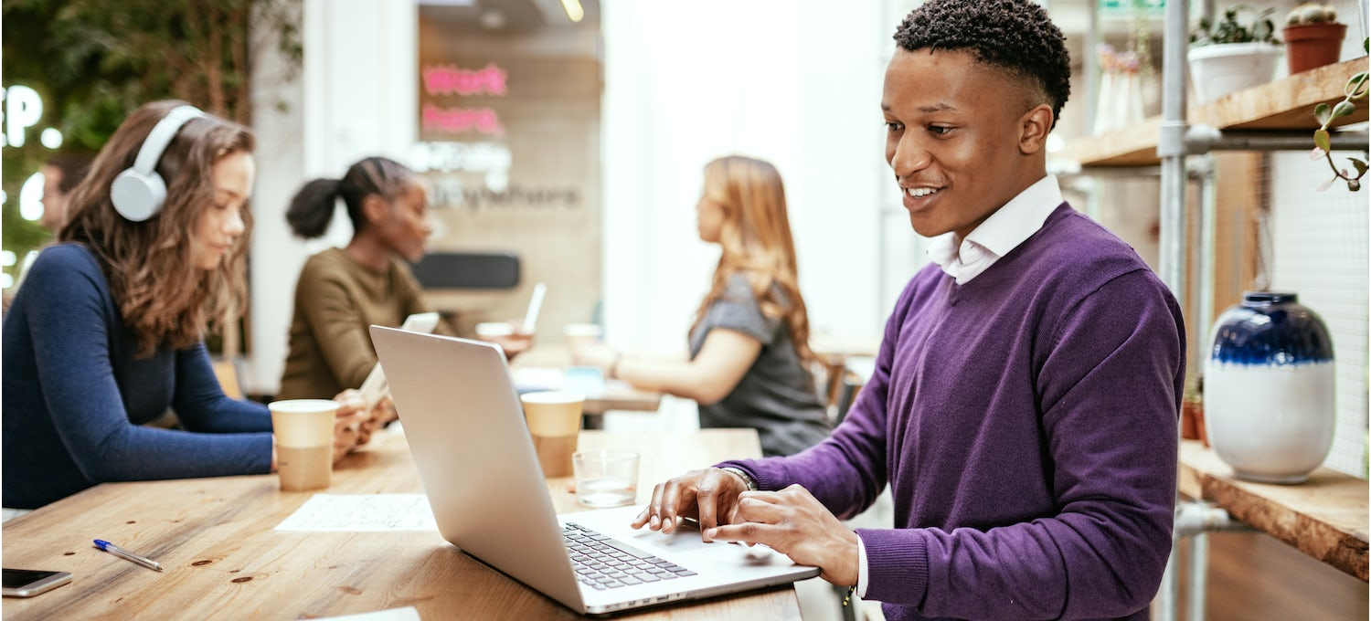 A man in a purple sweater and white collared shirt sits at his laptop in a bright cafe studying for a cloud security certification.