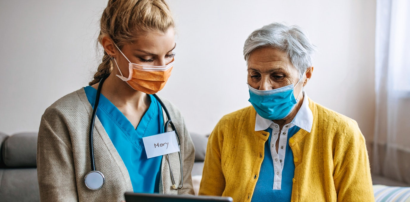 A younger nurse wearing a face mask, blue scrubs, and stethoscope assists an older women in a yellow sweater
