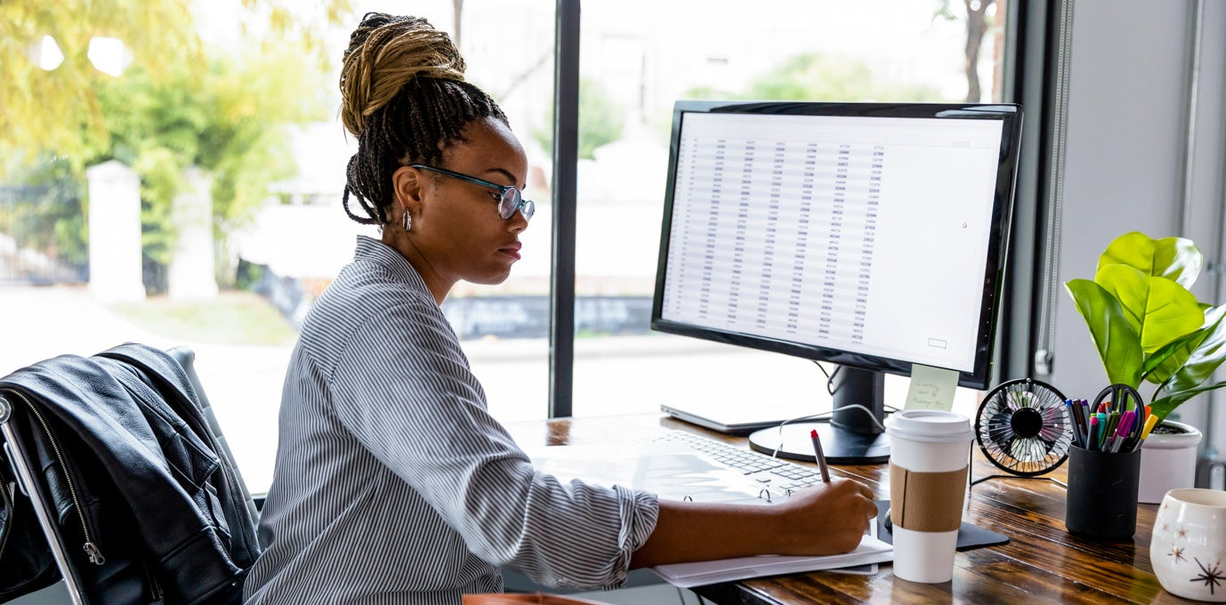 Professional business woman in glasses and a striped shirt sitting in front of a computer writing on a note pad