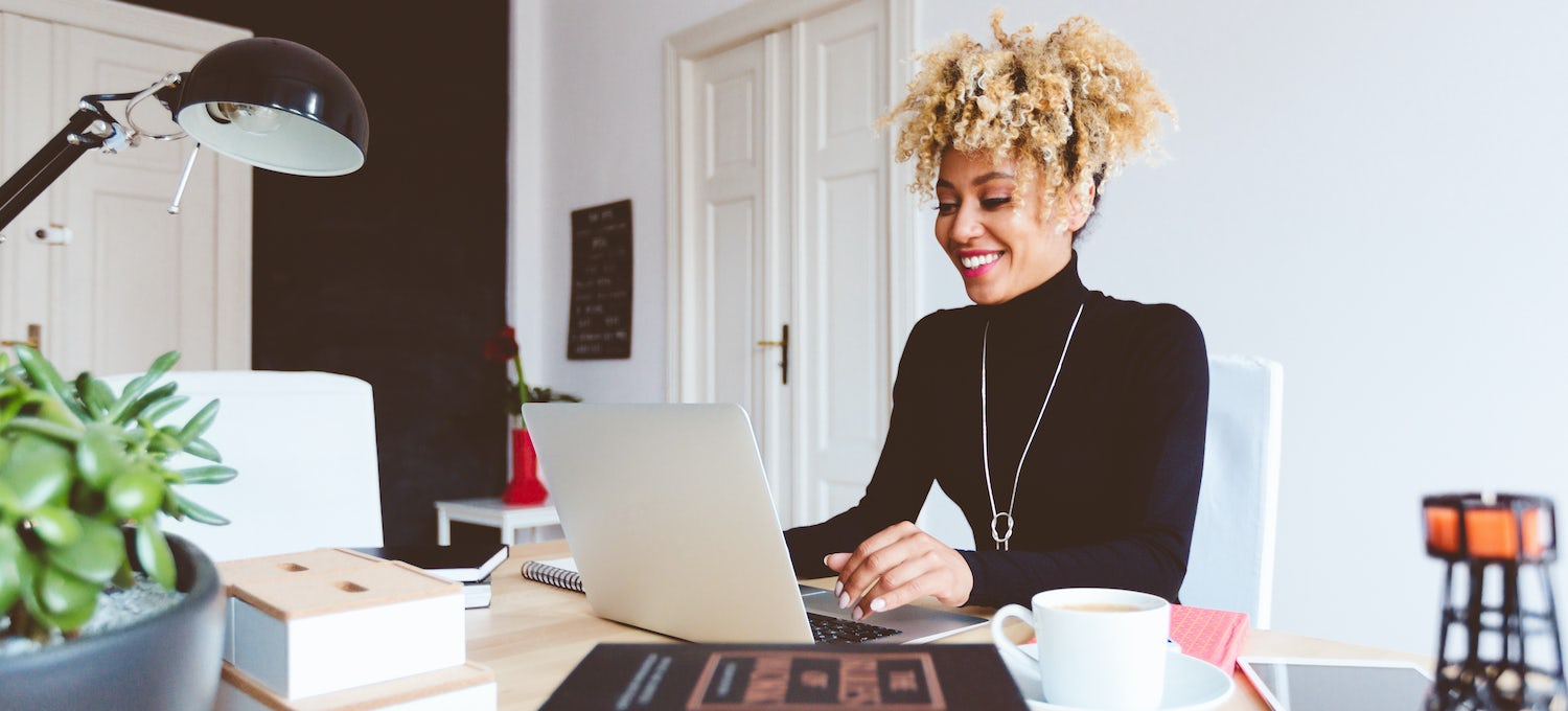 A smiling woman in a black shirt and necklace sits at her laptop working on her UX portfolio in a brightly lit office