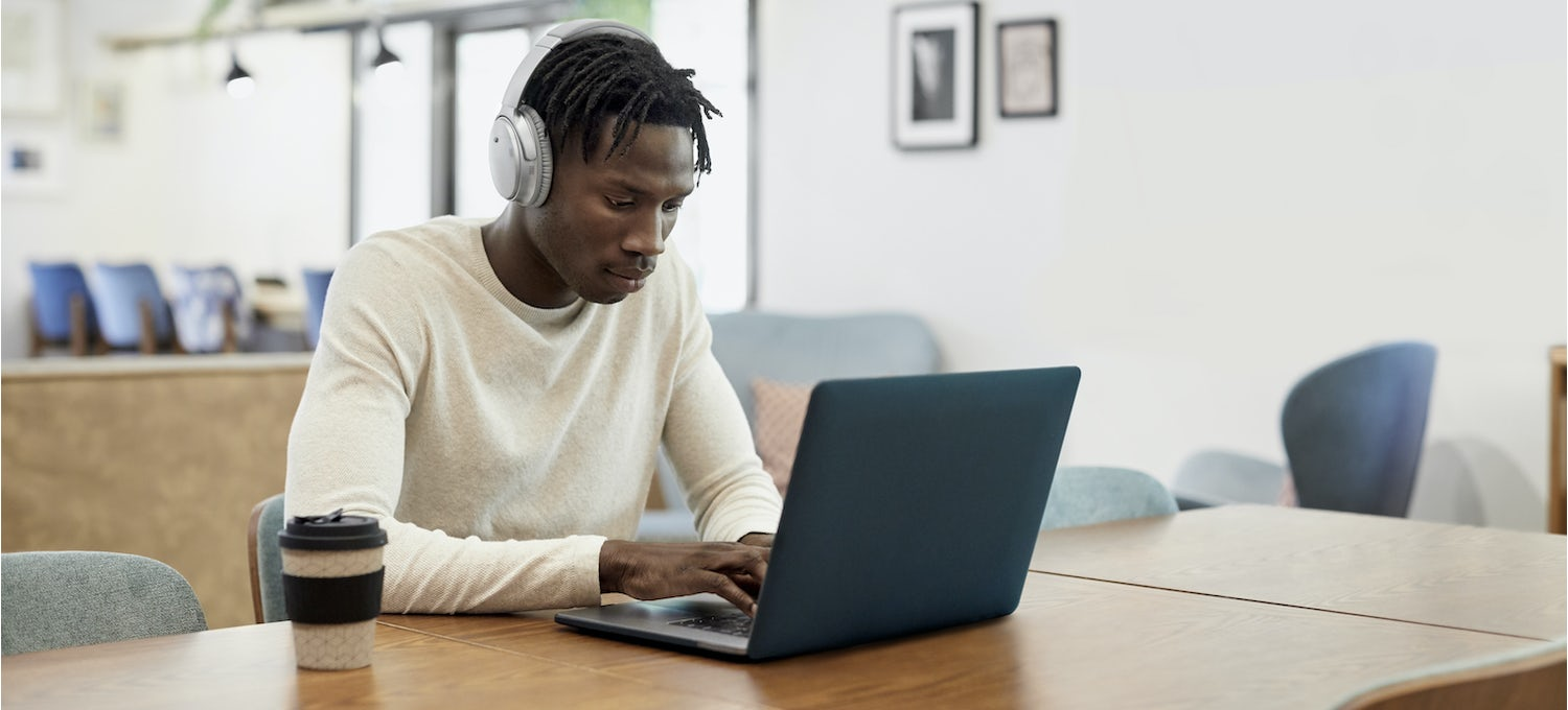 A man in a white sweater and headphones sits at his laptop preparing for an ethical hacking certification exam. A cup of coffee sits next to him on the table.