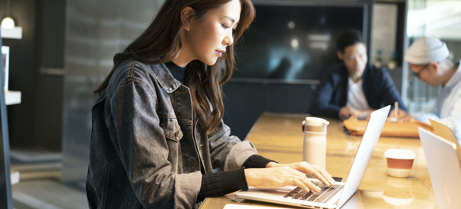A student in a cybersecurity degree program works at her laptop in a coffeeshop.