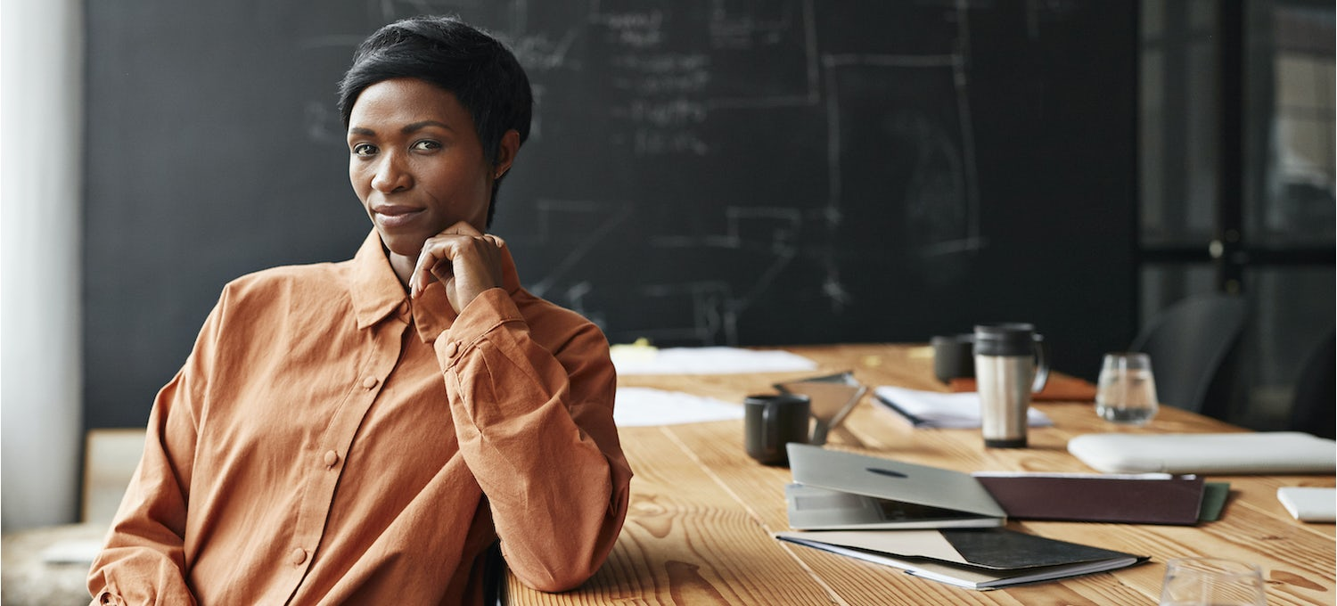 A project manager in an orange shirt sits at a work table with a laptop, tablet, and coffee mug with a blackboard in the background.