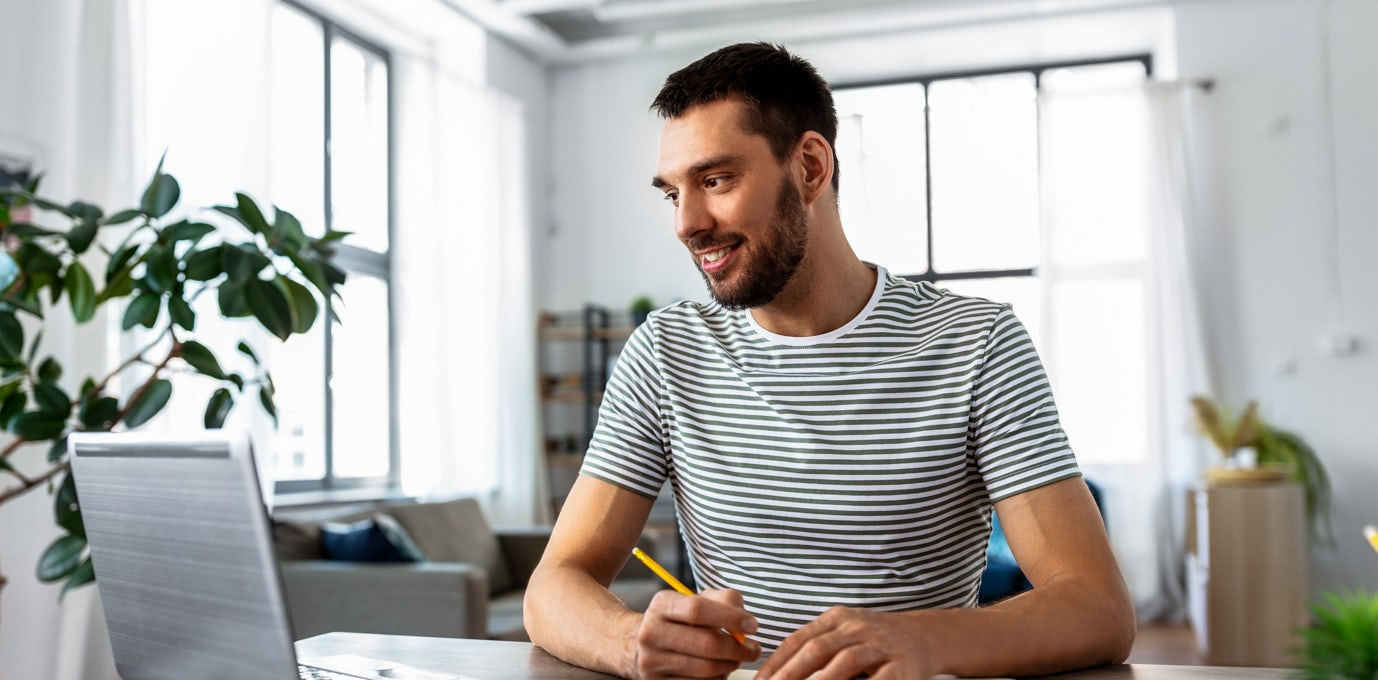 A man in a striped shirt sits in front of his laptop writing with a pencil and paper