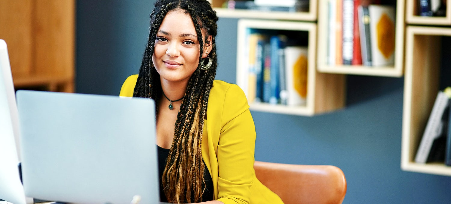 A cybersecurity analyst with braided hair and a yellow jacket sits in front of her laptop.