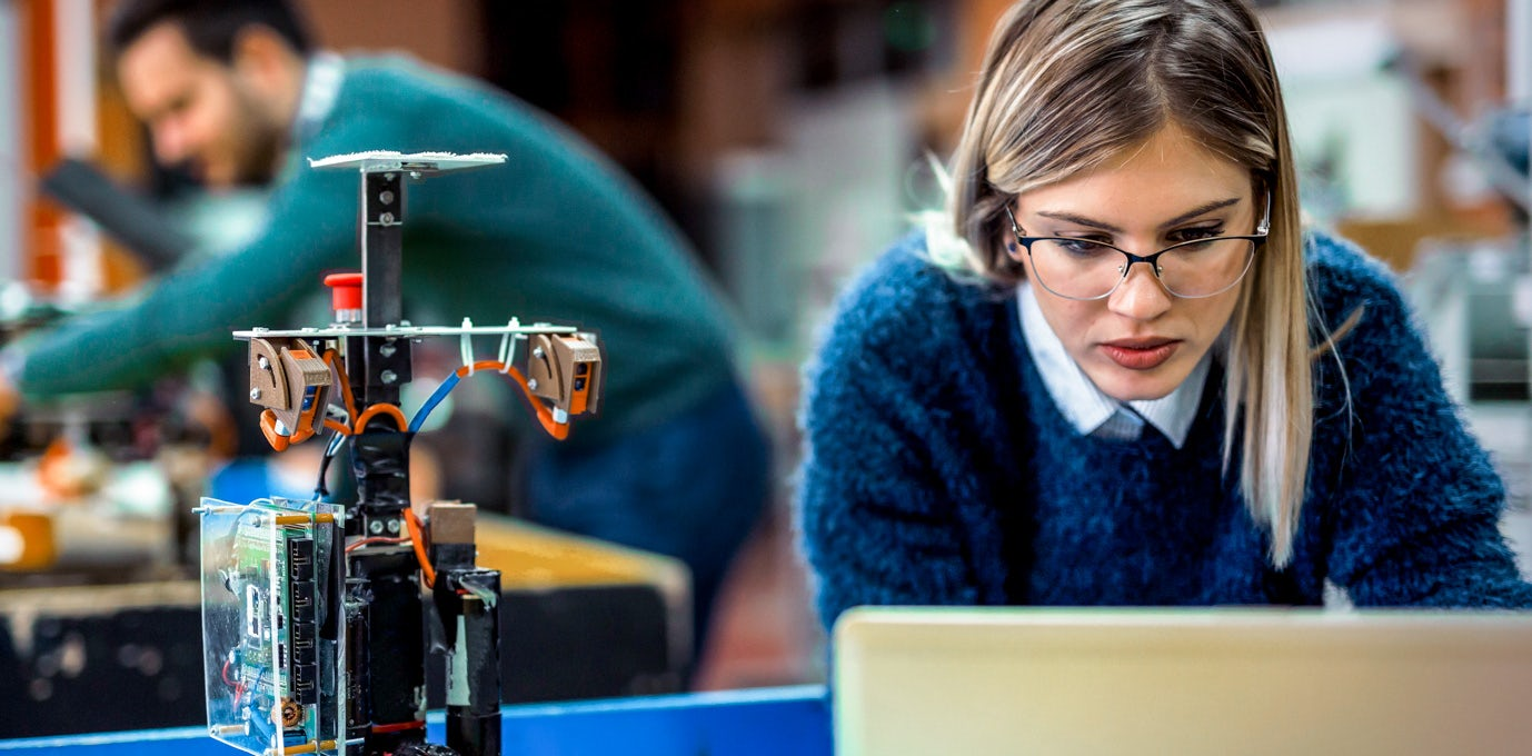 Blond woman in classes and a blue sweater working in front of a computer at a futuristic computer science lab