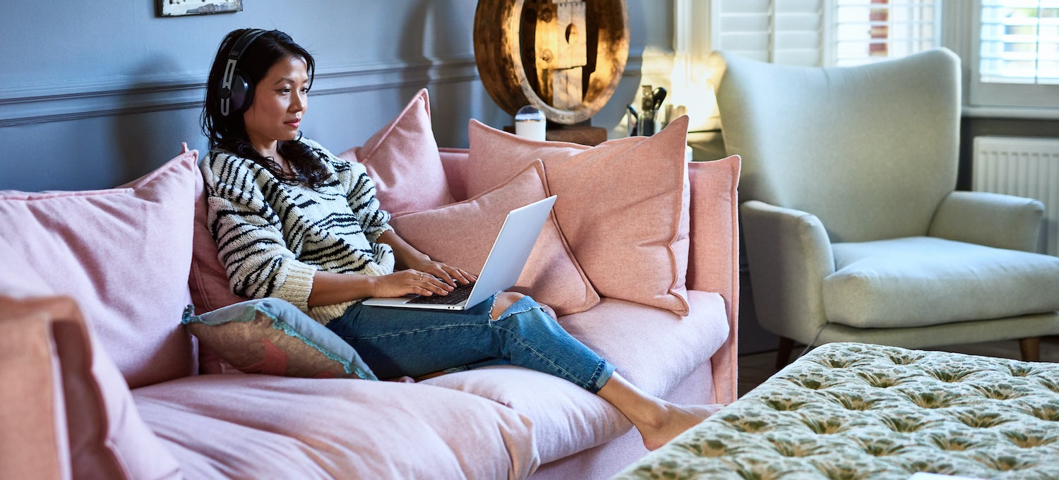 A software developer in a zebra striped shirt sits on a pale pink sofa with her laptop computer on her lap. She's wearing headphones.