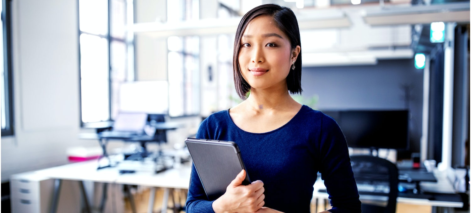 A woman in a blue shirt stands in front of her cybersecurity workstation holding a tablet in her hands.