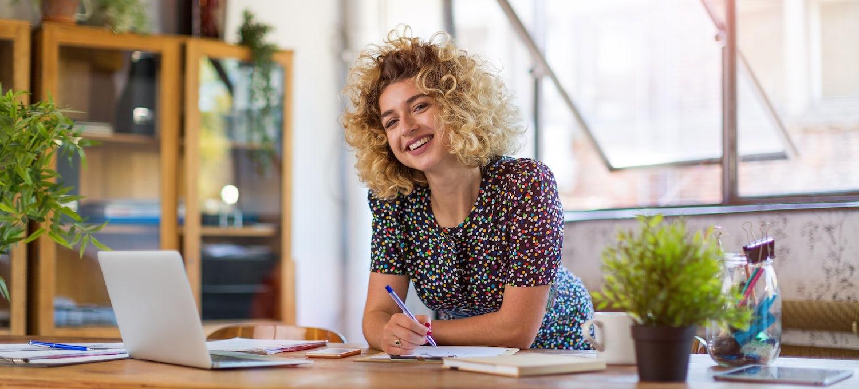 UX designer putting together her resume in her home office