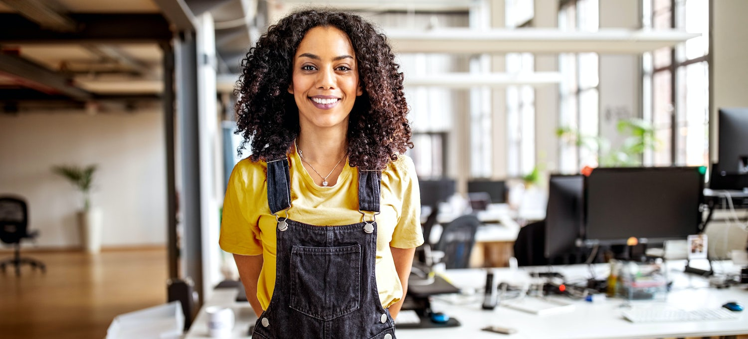 A woman in a yellow shirt and denim overalls works as a data architect in a bright office with computers on the desk behind her. She's smiling and looking at the camera.