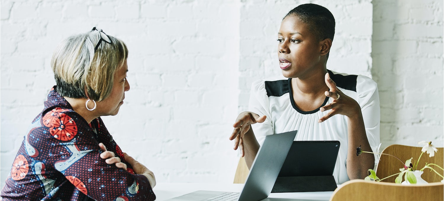 A female business analyst interviews a female employee. Both have their laptops in front of them.