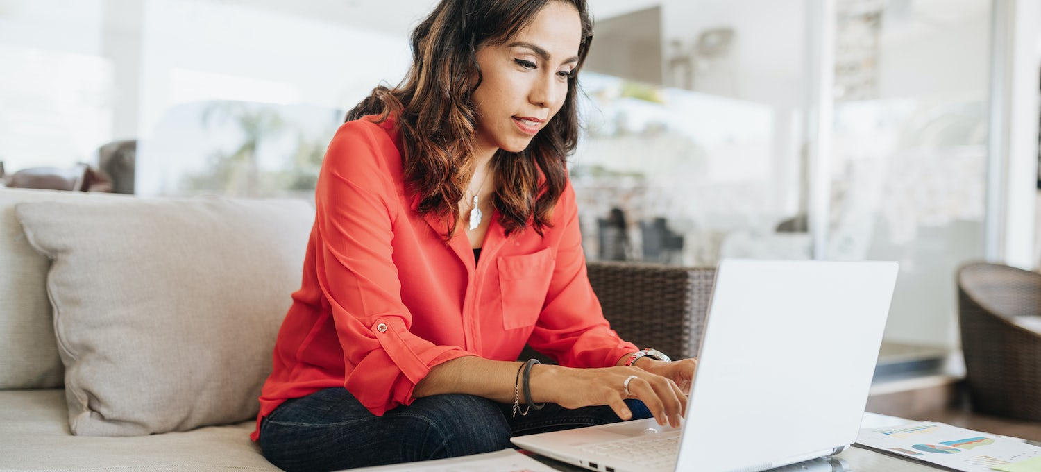 A woman in a coral colored shirt sits on a beige sofa studying for the SSCP cybersecurity certification on her laptop.