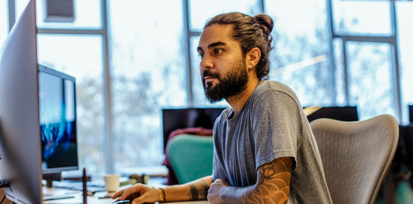 Tattooed male computer technician working at a dual screen workstation