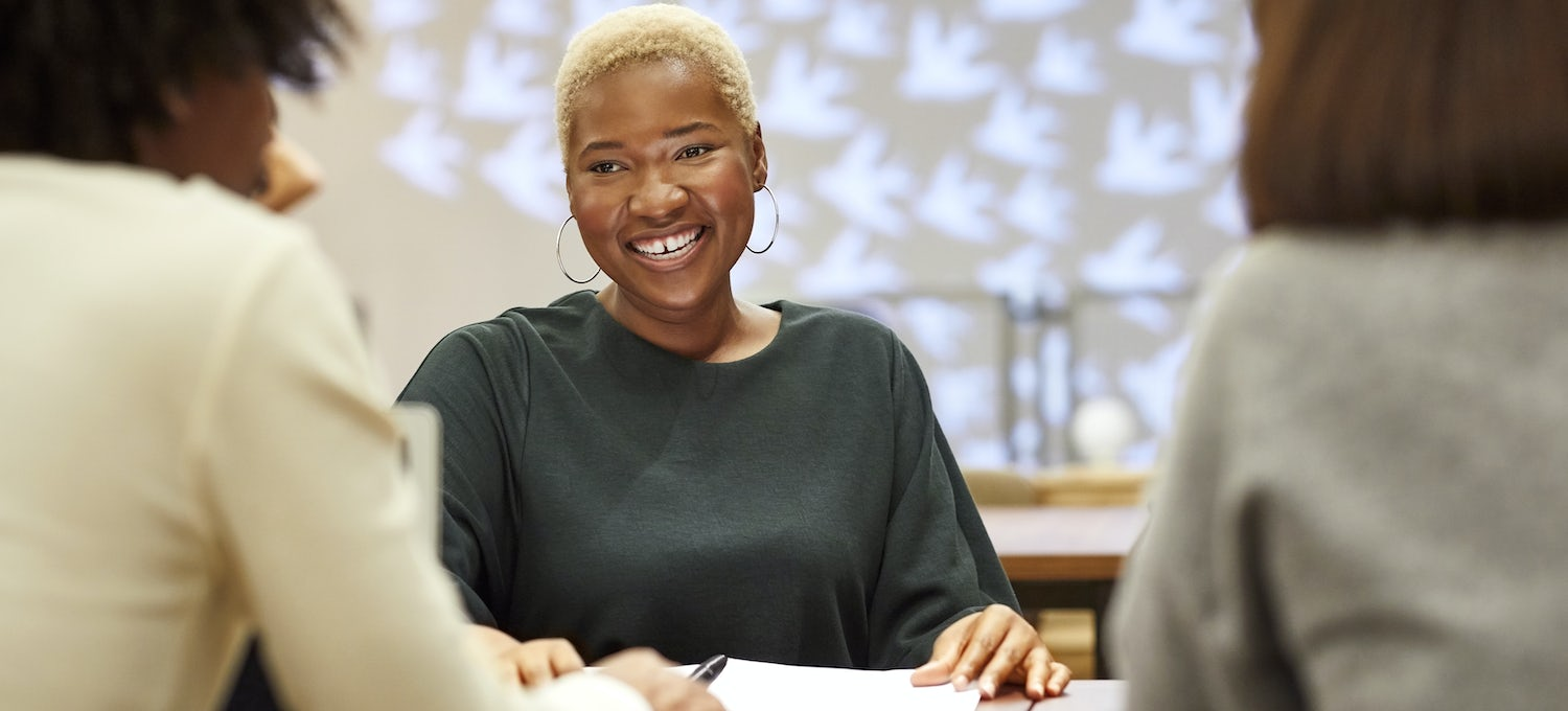 A smiling woman with short hair and earrings sits at a table during a UX designer job interview