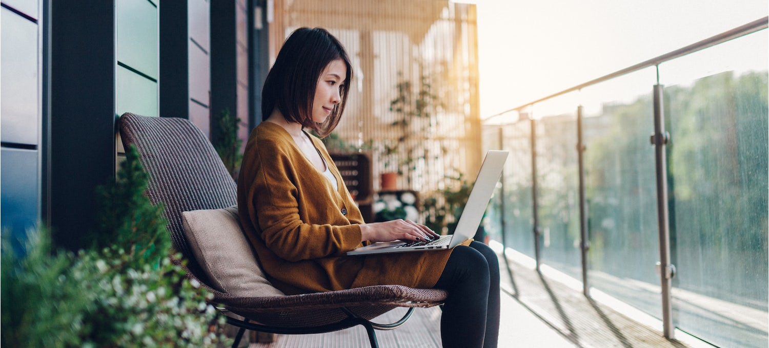 A woman sits on an outdoor patio with her laptop in her lap working on her portfolio