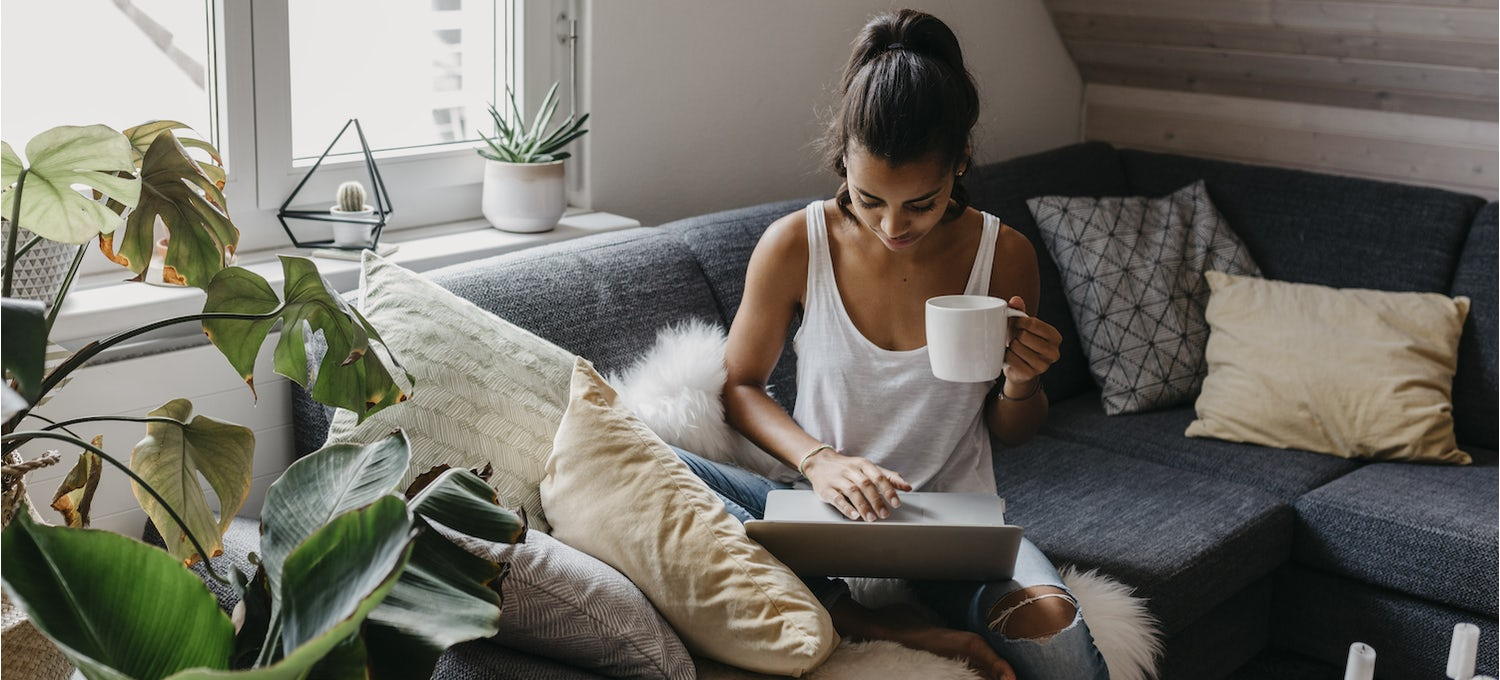 A woman sits on a couch, holding a white mug, as she types a cover letter on her laptop