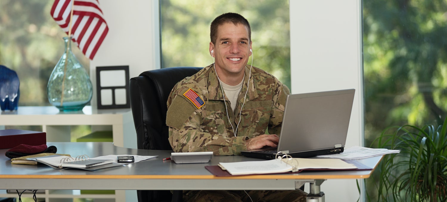 A man in military fatigues sits at a desk with a laptop. He's wearing headphones and smiling at the camera.