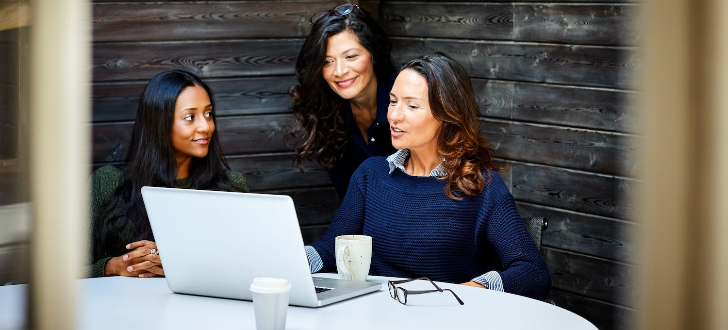 A marketing manager meets with her team at a conference table. One woman has a laptop, glasses, and a coffee cup in front of her.