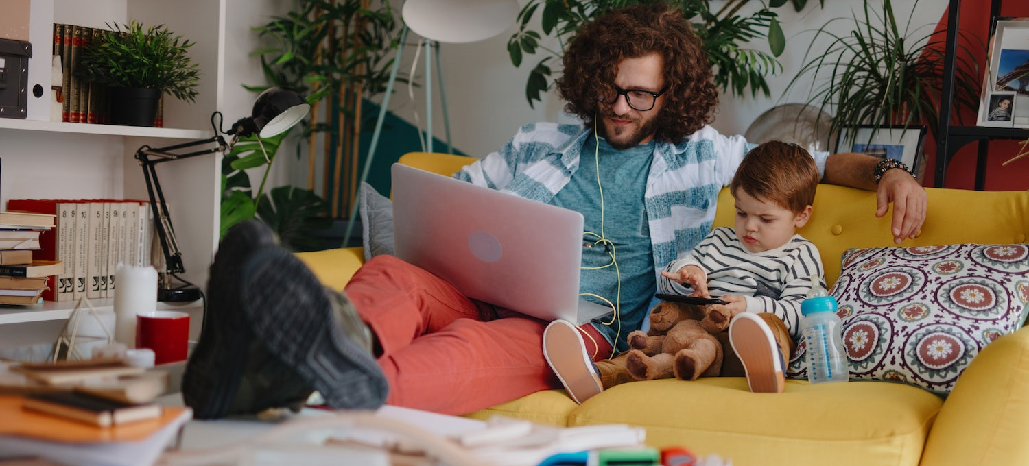 A man sits on a yellow sofa wit ha young toddler next to him. He's working on a college course on his laptop computer.